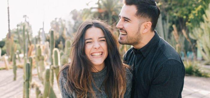 Pareja disfrutando de una risa íntima en un jardín de cactus