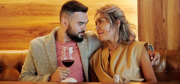 Pareja romántica sentada en un sofá mientras bebe vino