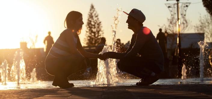Pareja sentada en cuclillas mientras se abrazan frente a una fuente de agua