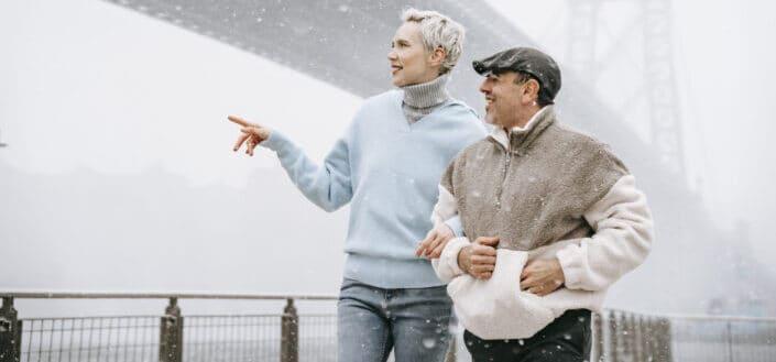 Una mujer más alta caminando del brazo con un hombre más bajo en una nieve fría