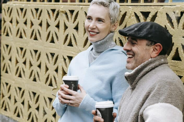 Hombre y mujer charlando mientras bebe café afuera en un clima frío