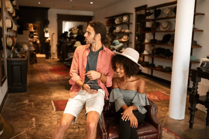 hombre y mujer sentados en una tienda de sombreros