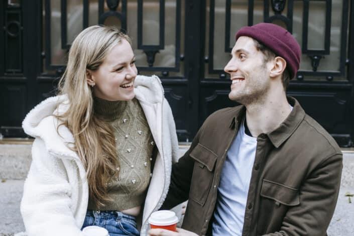 hombre y mujer alegres en una cálida charla fuera del clima frío