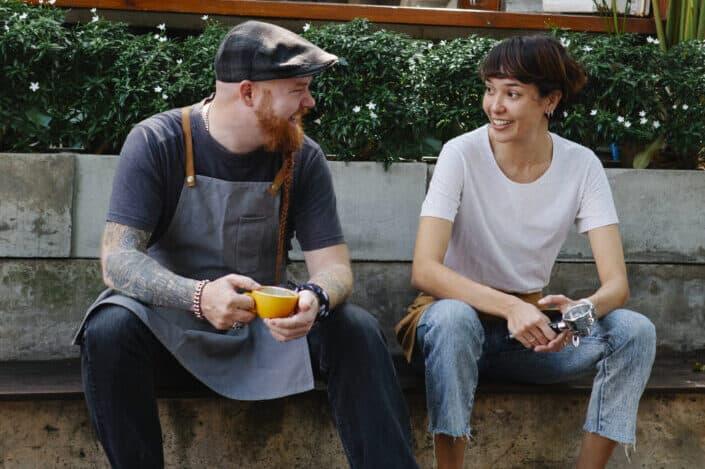 Mujer de aspecto masculino hablando con un hombre beardy tatuado en delantal