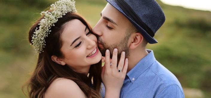 dulce hombre besando a su chica en las mejillas