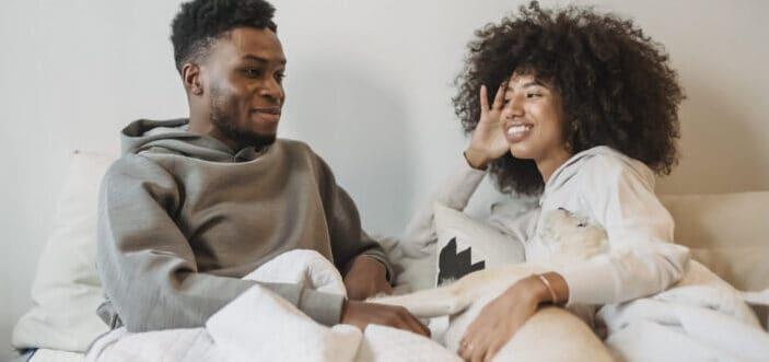 dulce pareja discutiendo mientras está acostado en su cama