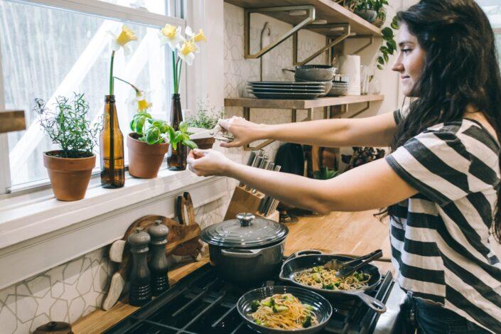 Mujer de pie delante de la estufa sosteniendo hojas de flores
