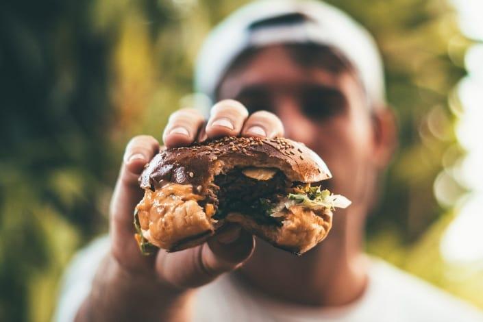 hombre mostrando la mitad de su hamburguesa