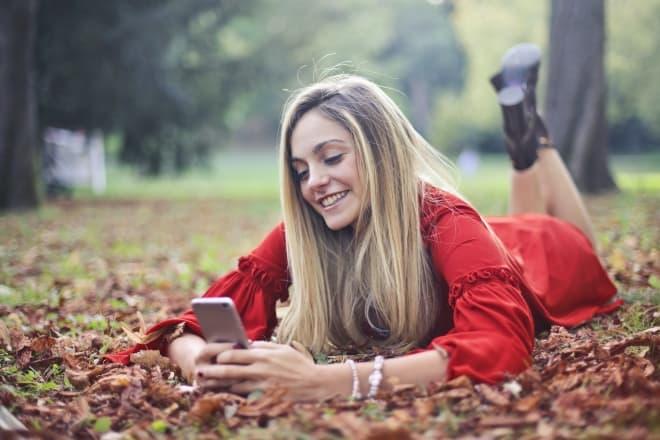 Mujer sonriente acostada sobre hojas secas mientras envía mensajes de texto - dares over text