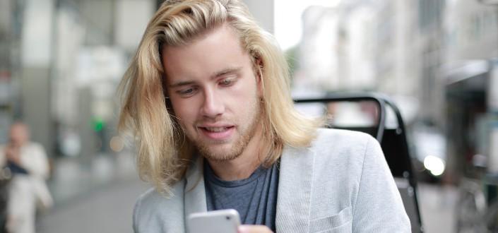 hombre sonriendo mientras dice en su teléfono